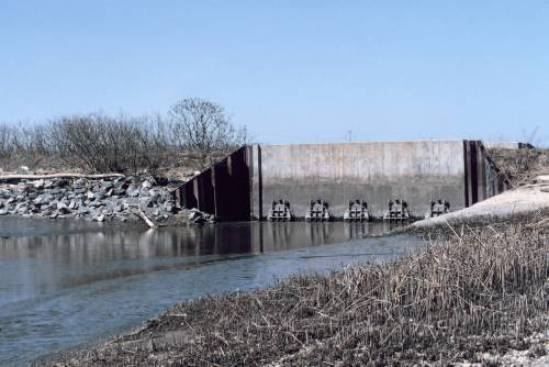 Figure 6.5 The tide gate at the mouth of Army Creek on the Delaware side of the Delaware River. The tide gate drains flood and rain water out of the creek to prevent flooding. The five circular mechanisms on the gate open and close to control water flow [Photo source: courtesy NOAA Photo Library].